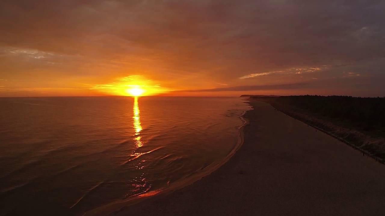 Zdjęcie przedstawiające wschód słońca naplaży wKarwi