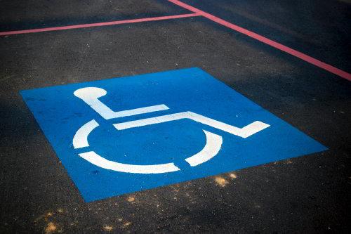 Ilustracja przedstawiajaca symbol oosby poruszajacej się przy pomocy wózka inwalidzkiego